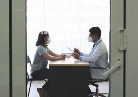médico conversando com paciente com máscaras foto