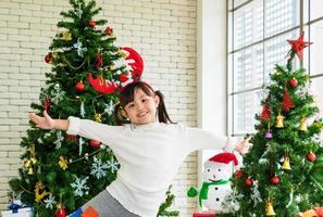 menina na frente da árvore de natal foto