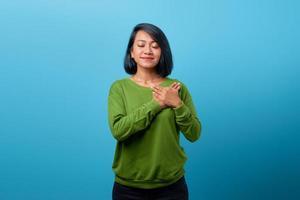 linda mulher asiática fechando os olhos e sorrindo, guardando memórias no coração foto