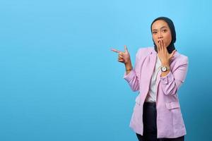 Mulher asiática surpresa apontando o dedo para o espaço vazio foto