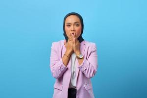 Mulher asiática surpresa cobrindo a boca com as mãos sobre um fundo azul foto