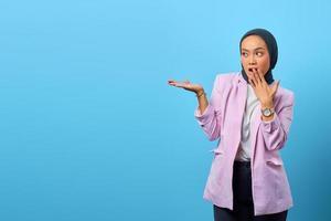 Mulher asiática surpresa mostrando produto em fundo azul foto