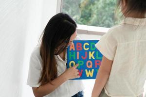 mãe ensinando a criança o alfabeto foto