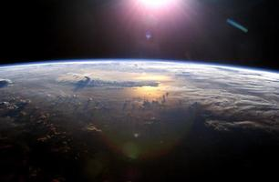vista do horizonte da terra enquanto o sol se põe sobre o oceano pacífico foto