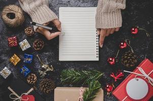 uma mão segurando uma caneta para escrever em um caderno com óculos foto