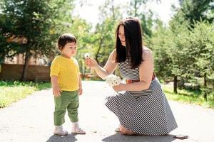 mãe passeando com a filha no parque dando flores para ela foto