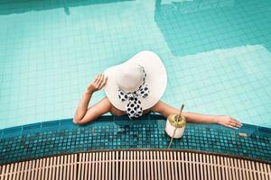 mulher de maiô relaxando na piscina foto