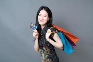 Mulher asiática usa vestido tradicional chinês com sacola de compras foto