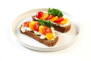 dois sanduíches com queijo macio e tomate foto