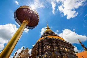 antigo antigo pagode dourado com um guarda-chuva de wat phrathat lampang luang templo com forma de estrela do sol no céu azul nublado, província de lampang, Tailândia. foto