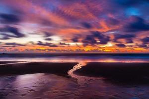 cena crepuscular da praia asiática com água corrente e nuvens. foto