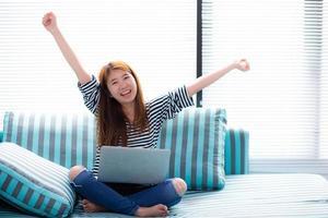 lindo retrato de felicidade de uma jovem mulher asiática usando laptop trabalhar com sucesso no sofá em casa, menina e notebook internet on-line com o conceito de comunicação feliz. foto