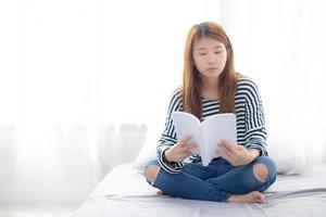 bela do retrato jovem mulher asiática relaxar sentado lendo livro no quarto em casa, literatura de estudo de menina, conceito de educação e estilo de vida. foto