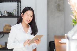 jovem mulher asiática usando computador tablet. foto