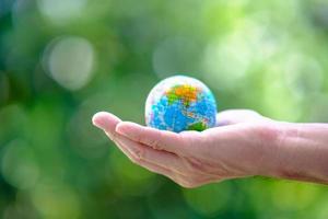 mão de negócios segurando um globo terrestre sobre fundo verde foto