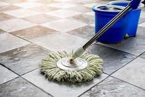 Limpe o piso de cerâmica com esfregões e produtos de limpeza de piso. foto