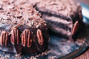 visão macro de um delicioso bolo de chocolate escuro com chips, bela cobertura e nozes pecan ao lado do prato de metal. foco seletivo. esmalte luxuoso. imagem para menu ou catálogo de confeitaria foto