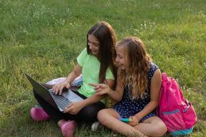 meninas com laptop e pastas fazendo lição de casa ou se divertindo foto