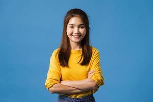 senhora asiática com expressão positiva, braços cruzados sobre fundo azul. foto