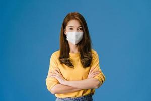 jovem asiática usa máscara facial com os braços cruzados sobre fundo azul. foto