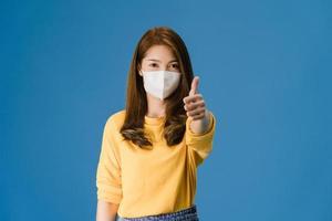 jovem asiática usa máscara facial aparecendo o polegar sobre fundo azul. foto