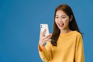 senhora asiática usando telefone com expressão positiva sobre fundo azul. foto