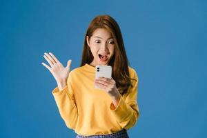 jovem usando telefone com expressão positiva sobre fundo azul. foto