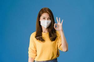 jovem asiática usa máscara facial gesticulando bem sinal sobre fundo azul. foto