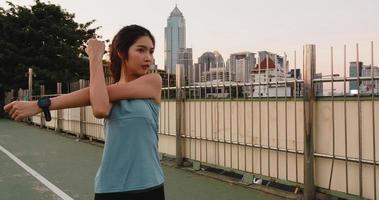 Ásia atleta senhora exercícios fazendo alongamento em urbano. foto