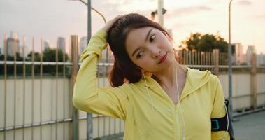 Ásia atleta senhora exercícios usando smartphone para ouvir música. foto