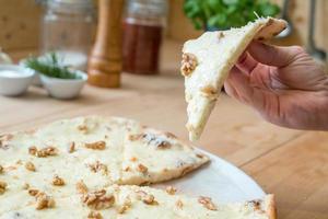 comendo uma fatia de pizza italiana de queijo gorgonzola e nozes foto