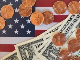 notas e moedas de dólar e bandeira dos estados unidos foto