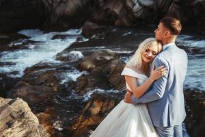 casal se abraçando com uma montanha e um rio ao fundo foto