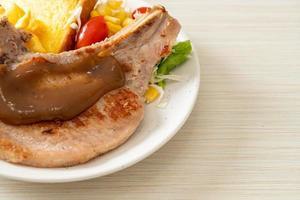 bife de porco com batata frita e mini salada foto