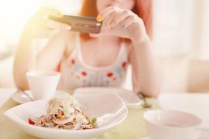 mulher ruiva tira fotos de salada na câmera do smartphone
