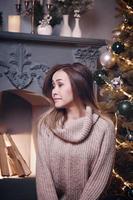 garota triste com suéter entre as decorações de natal foto