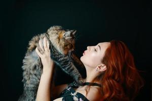 mulher ruiva abraça gato fofo em fundo preto foto