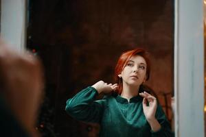 nobre garota ruiva se admira no espelho foto