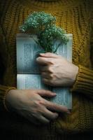 Mulher de suéter segurando um livro e um buquê foto