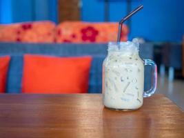 chá com leite fresco em um copo colocado sobre um piso de madeira. com espaço livre foto
