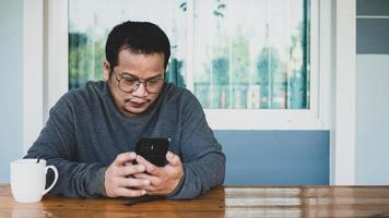 asiático está conversando no messenger de mídia social com um smartphone. foto