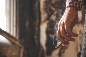 feche a mão masculina segurando um cigarro. foto