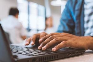feche as mãos tocando teclado no laptop foto
