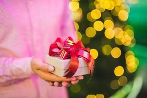 mãos segurando uma caixa de presente. conceito de felicidade, natal ou ano novo. foto