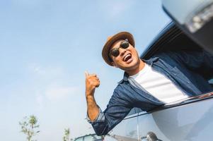 jovem bonito asiático dirigindo carro para viajar foto