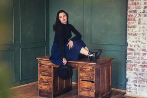 mulher posando em uma mesa de madeira foto