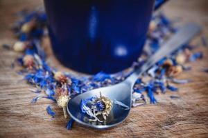 xícara e colher azuis com chá preto florido em um fundo de madeira foto