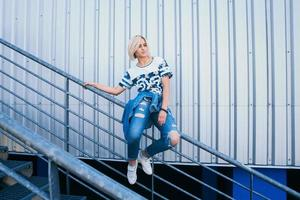mulher com cabelo branco curto em estilo urbano sentada na escada de metal foto