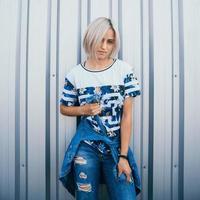 mulher com cabelo branco curto fica no fundo de uma parede de metal foto