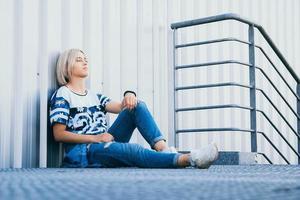 mulher com cabelo branco curto sentada no fundo de uma parede de metal foto
